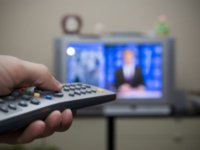 Person holds TV remote in front of television